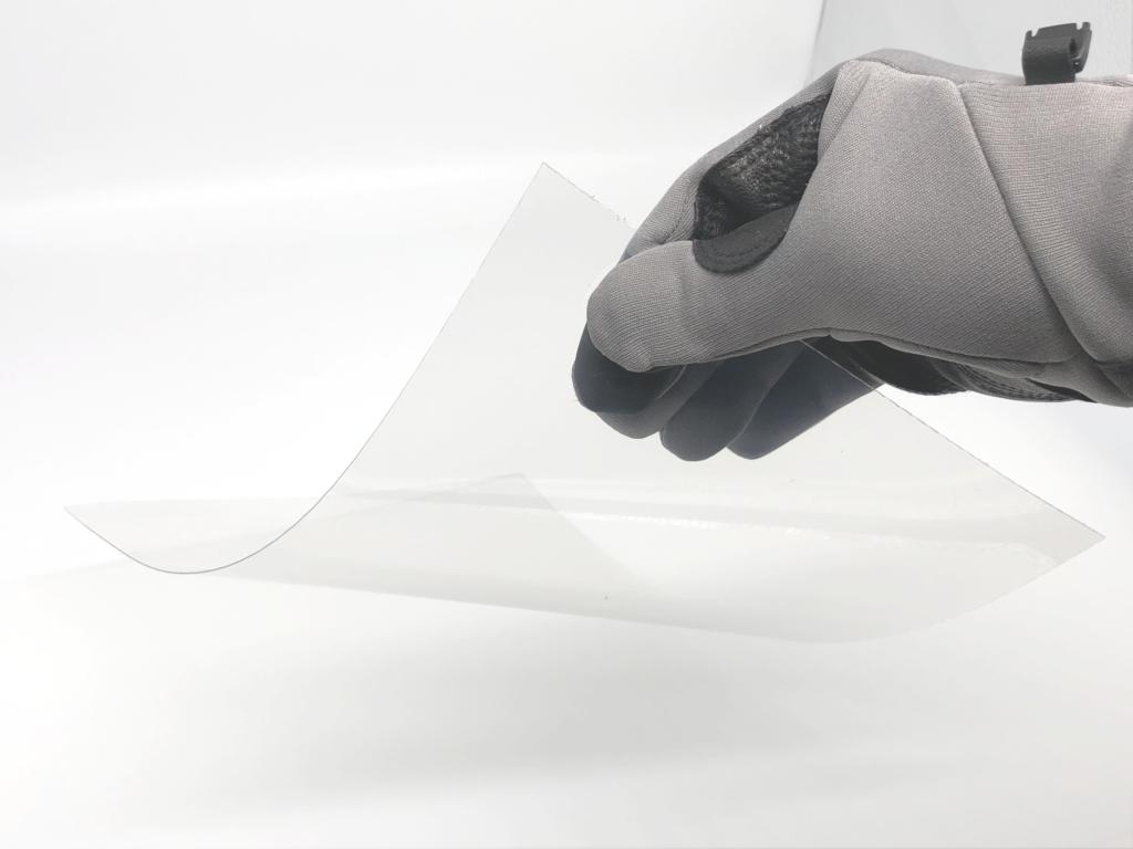 Schutzfolie für Strahlkabine mit einem Handschuh angehoben